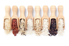 Wooden scoops with different rice types scattered from them Royalty Free Stock Photo