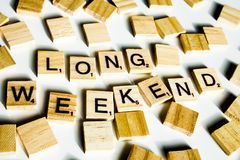 Wooden scrabble letters spelling the word LONG WEEKEND on white backround. stock images