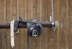 Wooden scramble with metal chain. A saddle placed on wooden scramble with metal chain Royalty Free Stock Photo