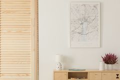 Wooden screen next to wooden cabinet with lamp, vase and heather in white pot, map in white frame on the wall. Real photo stock images