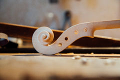 Wooden scroll detail of the head of the violin. Raw wood, texture. Against the background of workshop. Stock Image