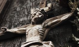 A wooden sculpture of crucified Jesus Christ  styled retro. Jesus Christ crucified an ancient wooden sculpture details Stock Photography