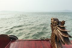 Wooden sculpture of dragon head at the back of tourist cruise moving on emerald water in golden hour at Quang Ninh, Vietnam Stock Images