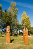 Wooden sculptures in the meadow in front of trees Stock Photo