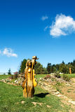 Wooden sculptures in the meadow in front of trees Royalty Free Stock Photography