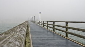 Wooden sea bridge of Zingst. View across the wooden sea bridge of Zingst in the fog, Germany Royalty Free Stock Photography