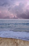 Wooden Sea Floor. Wood floor in place of sand with a colorful cloudy sunset and blue ocean Royalty Free Stock Photos