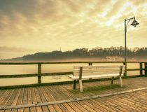 Wooden sea pier at misty morning with light posts. Heavy mist. Shaking above smooth Baltic sea. Foggy autumn weather Stock Images