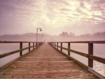 Wooden sea pier at misty morning with light posts. Heavy mist. Shaking above smooth Baltic sea. Foggy autumn weather Stock Image