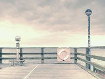 Wooden sea pier at misty morning with light posts. Heavy mist. Shaking above smooth Baltic sea. Foggy autumn weather Royalty Free Stock Photography