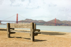 Wooden seat at the beach with Golden Gate bridge in the backgrou Royalty Free Stock Photography