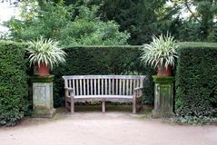 Wooden seat or bench and vases in a garden Stock Photos