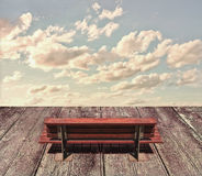 Wooden Seat and Sky. Digital collage technique photo composition about heaven, peace or reflexive concepts with wooden seat in the foreground and cloudy sky at Stock Image