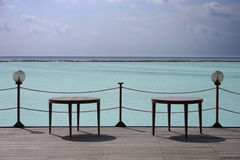 Wooden seats by tropical sea Royalty Free Stock Photography