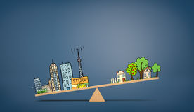 A wooden seesaw on blue background with an illustration of urban life overweighing a drawing of country houses. Stock Images