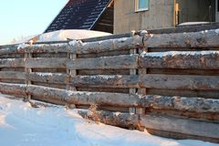 Wooden self-made fence of roughly hammered boards in the Siberian village in winter. Wooden self-made fence of roughly hammered boards in the Siberian village in royalty free stock images