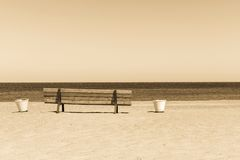 Wooden sepia bench on the sandy beach seashore Royalty Free Stock Images