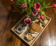 A wooden serving tray with traditional syrup waffles, coffee, su Royalty Free Stock Images