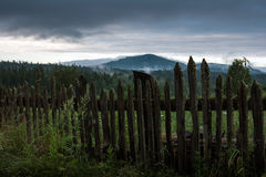 Wooden shabby fence against a mountain landscape Royalty Free Stock Images