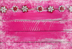 Wooden shabby pink background with garland of felt snowflakes Stock Images