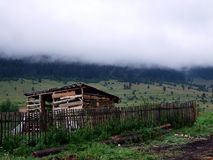 Wooden shack below misty mountain. Misty mountain in the background of a wooden shack Stock Image