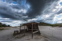 Wooden shack with dramatic clouds and sunbeam in background royalty free stock images