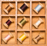 Wooden shadow box with thread spools Royalty Free Stock Photography
