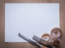 Wooden shavings flat chisels and clean sheet of paper on wood bo Royalty Free Stock Images