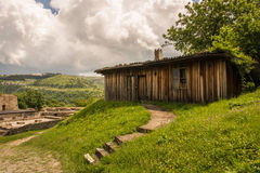 A wooden shed in the countryside. An aged wooden shed in the countryside, surrounded by green trees and grass, with mountains in the background Royalty Free Stock Photo