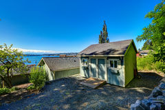 Wooden shed with white trim. Backayrd with beautiful bay view. P Stock Image