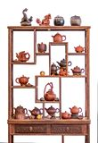 Shelf and ceramic teapots, cups, and other attributes for a traditional tea ceremony. Isolated on white background royalty free stock photo