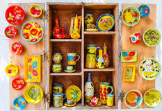 Wooden shelf of Greek souvenir store with Greek hand-made souvenirs - colorful ceramic cups and plates with pictures of cats, anim Stock Photography