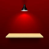 Wooden shelf illuminated by lamp Royalty Free Stock Photography