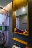 Wooden shelf and a mirror in bathroom Stock Photos