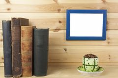 Wooden shelf with old books and picture frame Royalty Free Stock Image