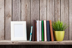 Wooden shelf with photo frames, books and plant Royalty Free Stock Photo