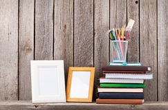 Wooden shelf with photo frames, books and supplies Stock Photo