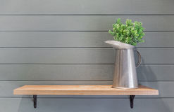 Wooden shelf on plank wall with vase of plastic flower Royalty Free Stock Images