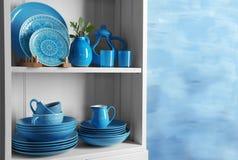 Wooden shelves with  rustic dinnerware. Wooden shelves with blue rustic dinnerware Stock Photography