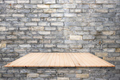 Wooden shelves and brick wall background. Stock Photo