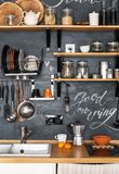Wooden Shelves with different jars on a black wall with chalk. Design of modern kitchen in loft and rustic style. Wooden Shelves with different jars on a black Royalty Free Stock Photography