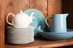Wooden shelves with white and blue   dinnerware. Wooden shelves with white and blue rustic dinnerware Royalty Free Stock Photos