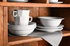 Wooden shelves with white   dinnerware. Wooden shelves with white rustic dinnerware Stock Image