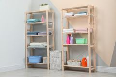 Wooden shelving units with clean towels and detergents. In stylish room interior royalty free stock images