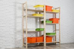 Wooden shelving units with colorful containers near white brick wall. Stylish room interior stock image
