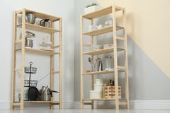 Wooden shelving units with kitchenware near color wall. Stylish room interior stock images