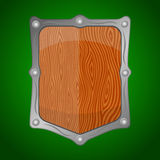 Wooden shield offering protection on green backgro Royalty Free Stock Photo