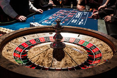 Wooden Shiny Roulette Details in a Casino and People. Wooden Shiny Roulette Details in a Casino with Blurry People and Croupier in Background stock photo