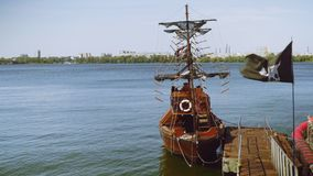 Wooden ship moored at pier with pirate flag and black sails. Wooden ship moored at the pier on the river embankment with a pirate flag and black sails stock video footage