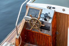 Wooden ship`s wheel in the cabin of the pleasure boat. Vintage wooden and brass ship`s steering wheel and control panel of a pleasure boat close up stock images